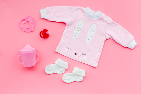 Newborn babys background. Clothes for small girl with booties on pink background top view