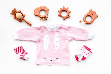 Newborn babys background. Clothes for small girl with booties on white top view