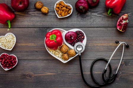 Products good for heart and blood vessels. Vegetables, fruits, nuts in heart shaped bowl near stethoscope on dark wooden background top view