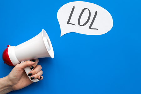 Reaction to something funny. Internet meme LOL. Megaphone near cloud with word LOL on blue background top view copy space