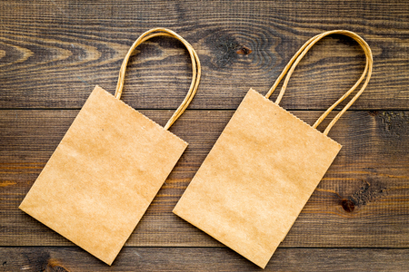 Brown kraft paper bag for shopping on wooden background top view.