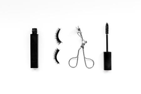 Cosmetics and tools for voluminous lashes. Mascara, false eyelashes, eyelash curler on white background top view. 스톡 콘텐츠
