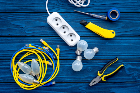Electrical repair. Bulbs, socket outlet, cabel, screwdriver, pilers on blue wooden background top view