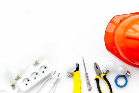 Electrician work concept. Hard hat, tools, socket outlet on white background top view