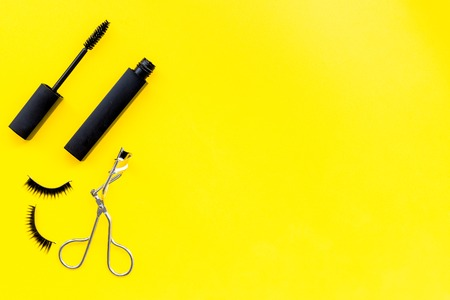 Makeup set for expressive eyelashes. Mascara, false eyelashes, eyelash curler on yellow background top view space for text 스톡 콘텐츠