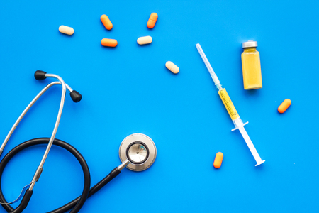 Medical examination and treatment concept. Stethoscope, syringe, pills on blue background top view