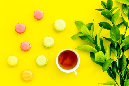 Summer mood, summer tea party. Cup of tea and sweets macarons near brignt greenery on yellow background top view