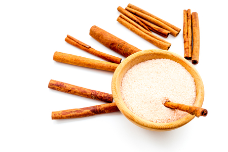 Cinnamon for cooking. Cinnamon sticks near bowl with sugar on white background.