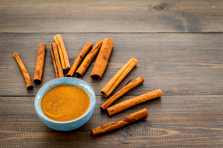 Cinnamon seasoning. Sticks and powder on dark wooden background.