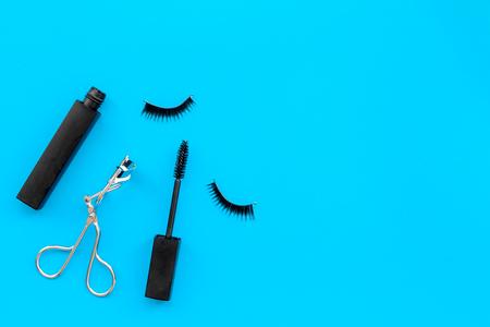 Cosmetics and tools for voluminous lashes. Mascara, false eyelashes, eyelash curler on blue background top view. Stock Photo
