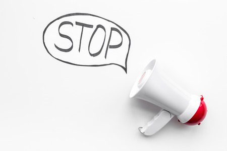 Demand to stop concept. Megaphone near cloud with word stop on white background top view.