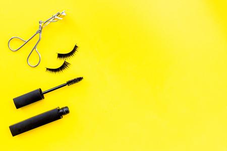 Makeup set for expressive eyelashes. Mascara, false eyelashes, eyelash curler on yellow background top view.