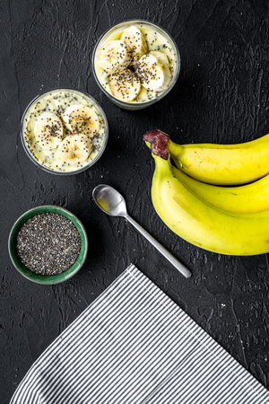 Banana pudding with chia seeds as low-calorie tasty appetizer. Black background with blue tablecloth top view. Stock Photo