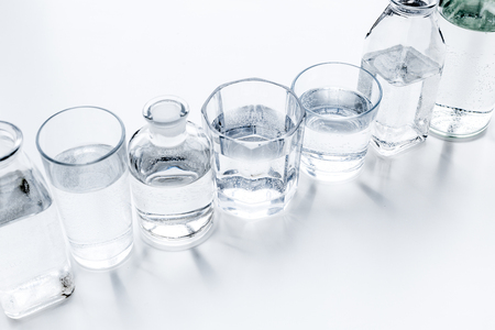 Drinks on the table. Pure water in jar and glasses on white background.
