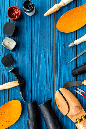 Instruments and materials for make shoes on blue wooden background top view.