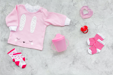 Newborn babys background. Clothes for small girl with booties on grey background top view.