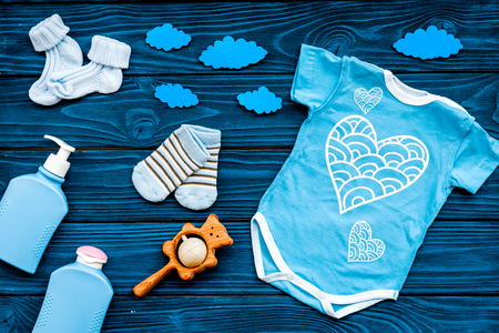 Newborn babys sleep concept. To put the child to bed. Baby bodysuit near clouds on blue wooden background top view.