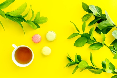Summer mood, summer tea party. Cup of tea and sweets macaroons near bright greenery on yellow background top view.