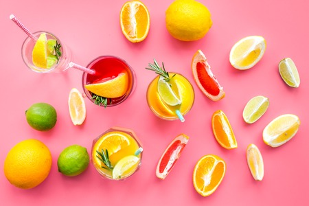 Tropical fruit cocktail with alcohol. Glass with beverage near oranges, grapefruit, lime and rosemary on pink background top view pattern Stock Photo