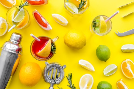 Mix exotic fruit cocktail with alcohol. Shaker and strainer near citrus fruits and glass with cocktail on yellow background top view pattern Stock Photo
