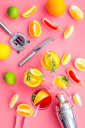 Mix exotic fruit cocktail with alcohol. Shaker and strainer near citrus fruits and glass with cocktail on pink background top view pattern