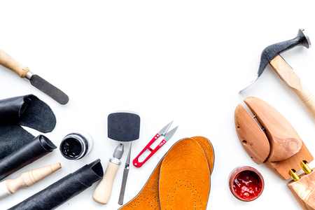 Work desk of shoemaker with instruments, wooden shoe and leather. White background top view.