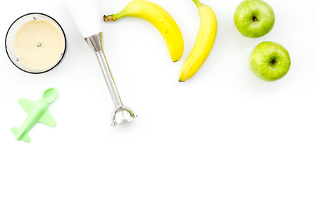Homemade baby food. Cook puree with apple and banana with immersion blender. White background with toy top view space for text 写真素材