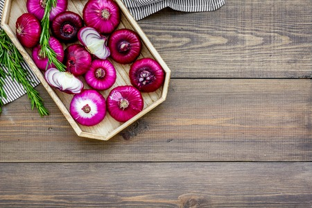 Red onion is healthy product. Onion bulbs in tray on dark wooden background top view copy space