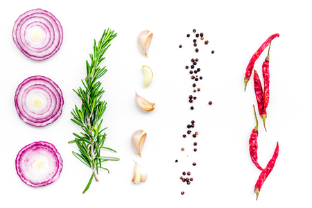 Red onion rings as seasoning. Onion near chili pepper, rosemary, black pepper, garlic on white background top view Stock Photo