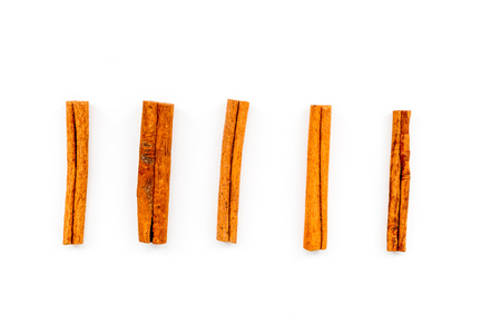Cinnamon sticks on white background top view. Condiment for mulled wine