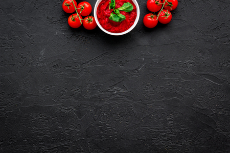 Tomato sauce in bowl with green basil near cherry tomatoes on black background top view space for text Stok Fotoğraf