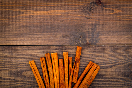Cinnamon sticks on dark wooden background top view copy space. Condiment for mulled wine