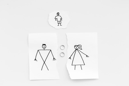 Child suffers from a divorce. Torn sheet of paper with drawn man, woman and child, wedding rings between parts on white background top view copy space 写真素材