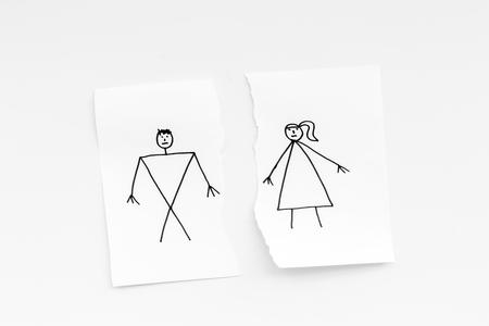 離婚または崩壊の概念。白い背景の上面図に描かれた男女との紙の破れたシート 写真素材