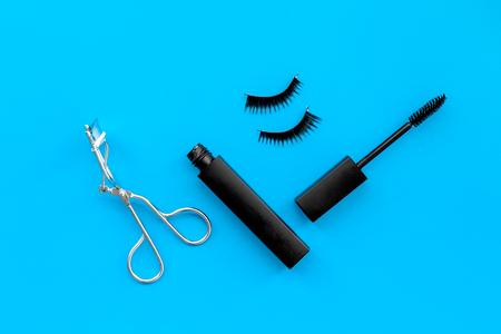 Cosmetics and tools for voluminous lashes. Mascara, false eyelashes, eyelash curler on blue background top view