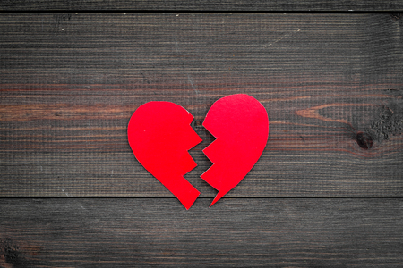 Divorce concept. Sign of divorce. Broken paper heart on dark wooden background top view copy space 스톡 콘텐츠