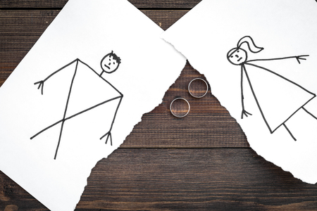 Divorce or falling apart concept. Torn sheet of paper with drawn man and woman, wedding rings between parts on dark wooden background top view copy space