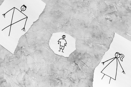 Child suffers from a divorce. Torn sheet of paper with drawn man, woman and child on grey background top view copy space
