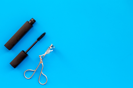 Basic products for eyelashes makeup. Mascara and eyelash curler on blue background top view copy space