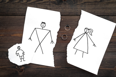Child suffers from a divorce. Torn sheet of paper with drawn man, woman and child, wedding rings between parts on dark wooden background top view Stock fotó
