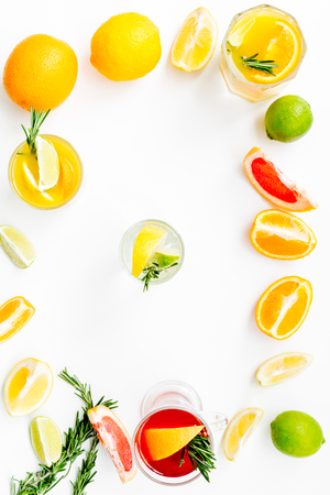 Concept of alcoholic cocktail with fruits. Glass with beverage near oranges, grapefruit, lime and rosemary on white background top view pattern