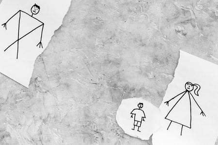 子供は離婚に苦しんでいる。灰色の背景トップビューコピースペースに描かれた男性、女性、子供と紙の破れたシート 写真素材