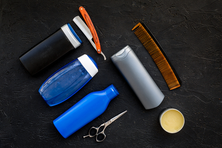 Mens set for everyday body, facial and hair care. Shampoo, gel, tools for brushing, scissor, comb on black background top view