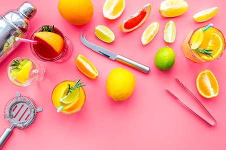 Bartender workplace for make fruit cocktail with alcohol. Shaker, strainer and other bar tools near citrus fruits and glass with cocktail on pink background top view.
