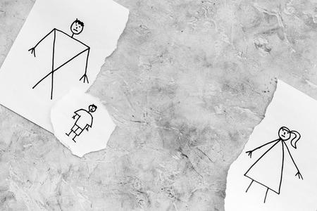 子供は離婚に苦しんでいる。灰色の背景の上面図に描かれた男性、女性、子供と紙の破れたシート。