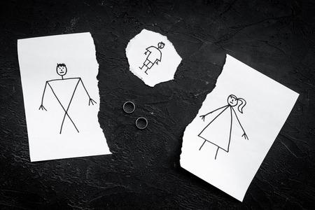 子供は離婚に苦しんでいる。描かれた男性、女性と子供と紙の破れたシート、黒の背景のトップビュー上の部分の間の結婚指輪。