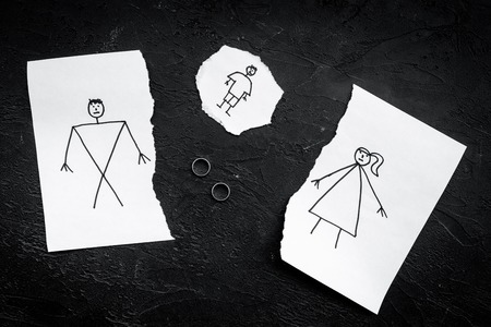 Child suffers from a divorce. Torn sheet of paper with drawn man, woman and child, wedding rings between parts on black background top view. Фото со стока