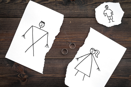 Child suffers from a divorce. Torn sheet of paper with drawn man, woman and child, wedding rings between parts on dark wooden background top view.