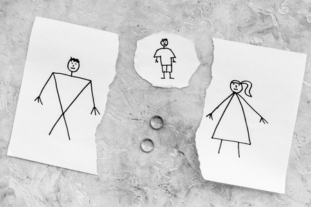 Child suffers from a divorce. Torn sheet of paper with drawn man, woman and child, wedding rings between parts on grey background top view.