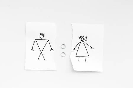 Divorce or falling apart concept. Torn sheet of paper with drawn man and woman, wedding rings between parts on white background top view . Banco de Imagens